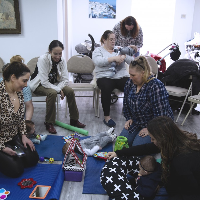 Class with parents and babies learning about toys that support infant development