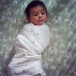 Baby swaddled in bed