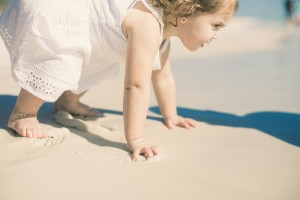 baby trying to stand in white dress on beach