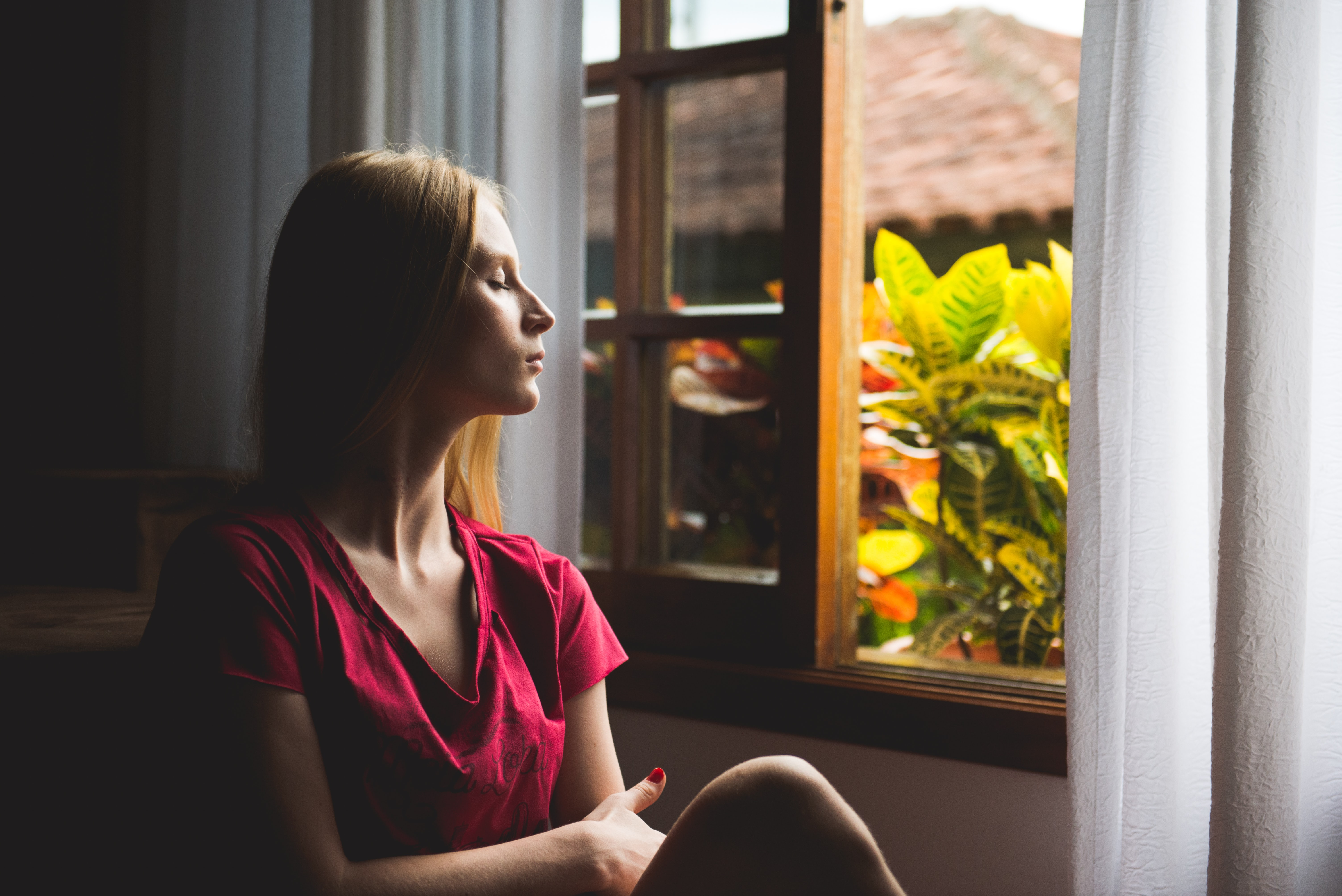 woman sitting near window looking out